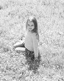 Flickan sitter p? gr?s p? grassplot, gr?n bakgrund Barnet tycker om soligt v?der f?r v?ren, medan sitta p? ?ngen heyday royaltyfria foton