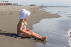 Flickan sitter på vattnets kant Arkivbild