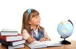 flickan sitter tabellen skriver Royaltyfria Bilder