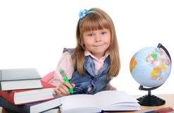 flickan sitter tabellen skriver Royaltyfria Foton