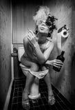 flickan sitter toaletten arkivfoto