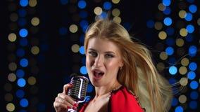 Flickan sjunger driftiga sånger i de bakgrund färgade ljusen Slapp fokus lager videofilmer