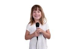 Flickan sjunger med en mikrofon i händer Arkivfoton