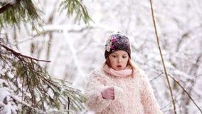 Flickan skakar snön från trädfilialen i den lyckliga barndomen för skogen körning av rolig pulkavinter arkivfilmer