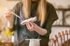Flickan skallr målarfärgborstar med keramisk krukmakeri i det idérika seminariet royaltyfri bild