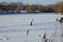 Flickan skidar på en djupfryst flod Royaltyfri Bild