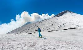 Flickan skidar turnera under överkanten av krater av Mount Etna Arkivbild