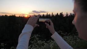 Flickan skjuter och tar bilder av solnedgången genom att använda en smartphone stock video