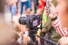 Flickan skjuter på kameran och tar bilder på telefonen royaltyfria bilder