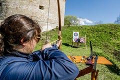 Flickan skjuter pilar från väggarna av fästningen i den Staraya knatten Arkivfoto