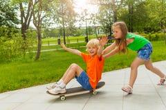 Flickan skjuter pojken med armar ifrån varandra på skateboarden Arkivbilder