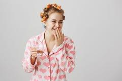 Flickan skrattar över hennes blick medan nära spegeln Stående av den gulliga europeiska flickan, i papiljotter och att rymma för  Royaltyfri Foto