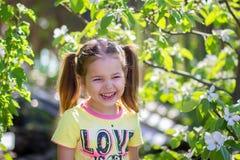 Flickan skrattar anseende nära det blomstra trädet Arkivfoton