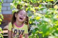 Flickan skrattar anseende nära det blomstra trädet Royaltyfri Bild