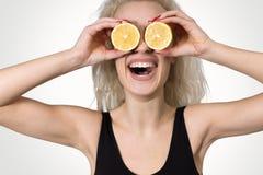 Flickan skrattar i händerna av en citrusfrukt Arkivfoton