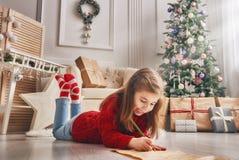 Flickan skrivar brevet till Santa Claus Royaltyfri Fotografi