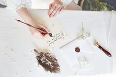 Flickan skrivar ett brev till hennes älskade man som hemma sitter på tabellen i en klänning, en renhet och en harmlöshet för vitt royaltyfria bilder