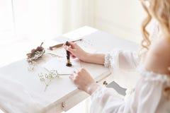 Flickan skrivar ett brev till hennes älskade man som hemma sitter på tabellen i en klänning, en renhet och en harmlöshet för vitt royaltyfri bild