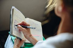 Flickan skriver den aktuella affären på böckerna arkivfoton