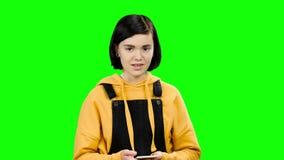Flickan skriver ett meddelande på hennes smartphone grön skärm lager videofilmer