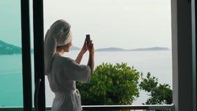 Flickan skriver ett meddelande på smartphonen på härlig sikt för semester arkivfilmer