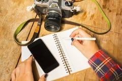Flickan skriver i anteckningsbok med mobiltelefonen och kameran Arkivbilder