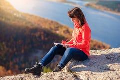 Flickan skriver i en anteckningsbok Arkivbilder