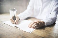 Flickan skriver i en dagbok på en trätabell med koppen kaffe Arkivbild