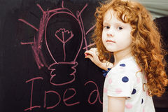 Flickan skriver i krita på en svart tavla Arkivbild