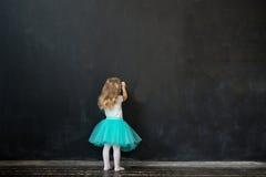 Flickan skriver med krita på en svart tavla Royaltyfri Fotografi