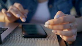 Flickan skriver på en smartphone En brunett i ett grov bomullstvillomslag sitter med en bärbar dator och en smartphone på en tabe arkivfilmer