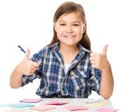Flickan skriver på färgklistermärkear som använder pennan Royaltyfria Foton