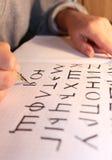 Flickan skriver slaglängder. Royaltyfri Fotografi