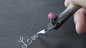 Flickan skriver vitt färgpulver på svart papper