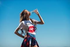 Flickan släcker törstat mot himlen Kvinnadricksvatten från en flaska arkivbild
