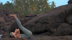 Flickan slår en kullerbytta tillbaka på stort plant vaggar ultrarapid stock video