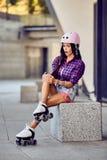 Flickan slogg benet under att åka skridskor för rulle Arkivfoto