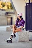 Flickan slogg ett ben, medan rullen som åker skridskor i stads- skridsko, parkerar royaltyfri bild