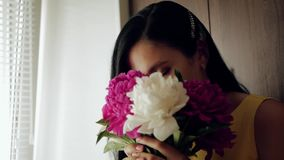Flickan sniffar blommor En härlig vit flicka kommer med en bukett av pioner till hennes framsida och inhalerar deras doft, då bli lager videofilmer