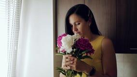 Flickan sniffar blommor En härlig vit flicka kommer med en bukett av pioner till hennes framsida och inhalerar deras doft, då bli arkivfilmer