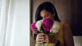 Flickan sniffar blommor En härlig vit flicka kommer med en bukett av pioner till hennes framsida och inhalerar deras doft lager videofilmer
