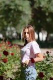 Flickan sniffar en röd blomma tonåringflicka som luktar rosor arkivfoto