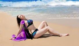 Flickan solbadar i baddräkt på sanden nära havet Fotografering för Bildbyråer