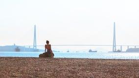 Flickan solbadar i morgonsolen på bakgrunden av den ryska bron på den Russky ön över den östliga Bosphorusen in royaltyfri bild