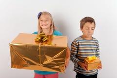 Flickan som är lycklig med en stor närvarande ask men hennes broder, har endast en sma Fotografering för Bildbyråer