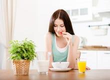 Flickan som äter jordgubben med, mjölkar och orange fruktsaft royaltyfri foto