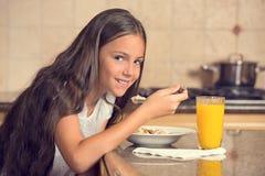 Flickan som äter sädesslag med, mjölkar att dricka orange fruktsaft för frukost Arkivfoto