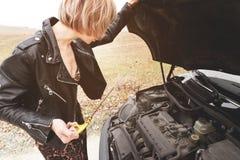 Flickan som öppnar huven av hennes bil, kontrollerar den olje- nivån för motorn Royaltyfri Foto