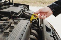 Flickan som öppnar huven av hennes bil, kontrollerar den olje- nivån för motorn Arkivbilder