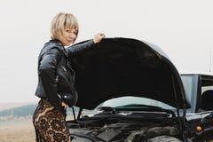 Flickan som öppnar huven av hennes bil, kontrollerar den olje- nivån för motorn Royaltyfri Bild